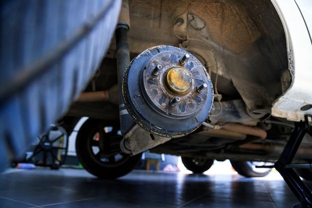 Un mozzo posteriore dell'auto dopo aver rimosso un pneumatico e una ruota, mantenendo un sistema di freno e ruota, sollevamento dell'auto per cambiare una ruota dell'auto, primo piano