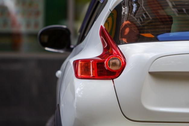La luce posteriore di un'auto parcheggiata vicino al marciapiede sul lato della strada in un parcheggio.