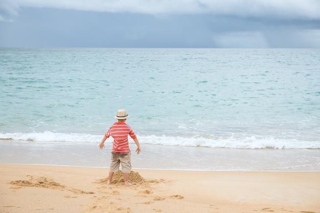 La parte posteriore del ragazzino con il cappello gioca con la sabbia sulla spiaggia con l'onda del mare di movimento, phuket, tailandia. attività di vacanza per bambini in estate.