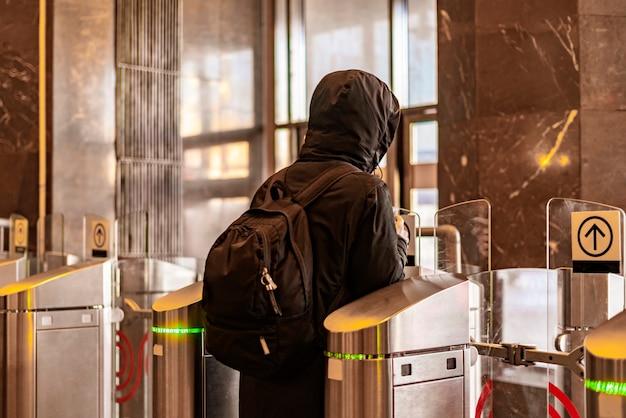 Il ritratto posteriore della persona passa attraverso il tornello di sicurezza b