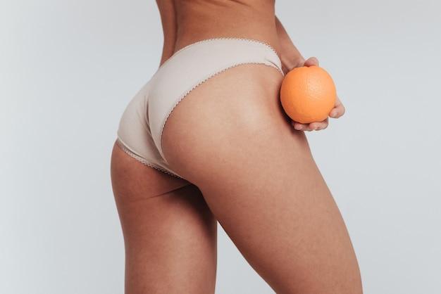 Parte posteriore e destra del corpo. foto di particelle di ragazza in biancheria intima bianca in piedi al muro bianco e tenendo l'arancia.