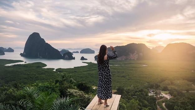 La parte posteriore della donna in viaggio sul ponte di legno guarda la splendida vista della baia di phang nga all'alba e alza la mano dal punto di vista samed nang chee, thailandia famosa meta di viaggio.