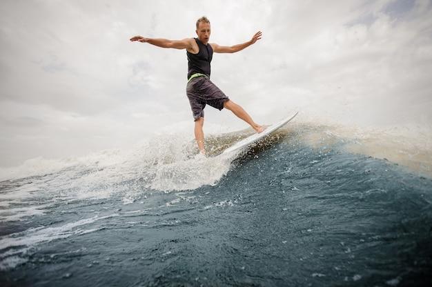 Uomo attivo di retrovisione che guida sul wakeboard
