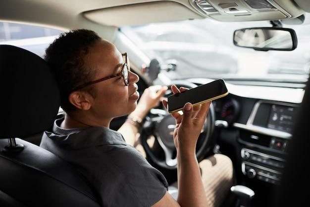 Vista posteriore di una donna africana con gli occhiali che parla al cellulare durante la sua guida
