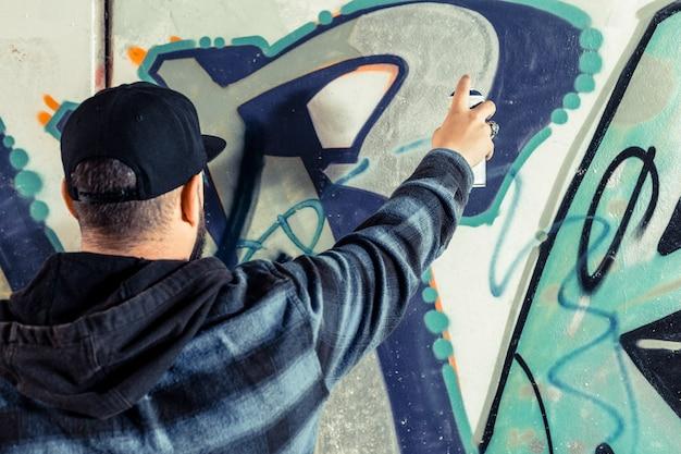 Vista posteriore di un artista che dipinge graffiti su un muro