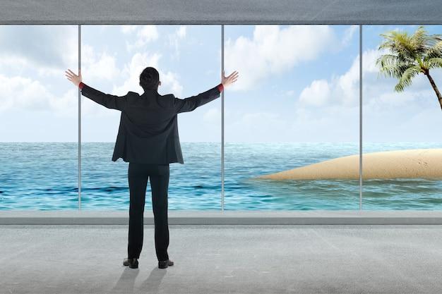 Vista posteriore dell'uomo d'affari asiatico che si gode una vacanza con vista sull'oceano dall'hotel