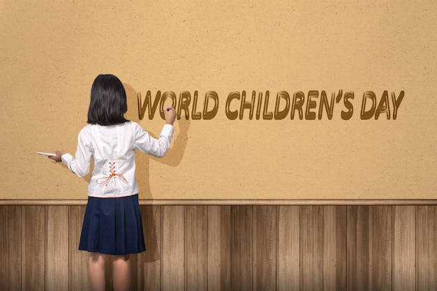 Vista posteriore della ragazza asiatica carina che dipinge un testo della giornata mondiale dei bambini sul muro. giornata mondiale dell'infanzia