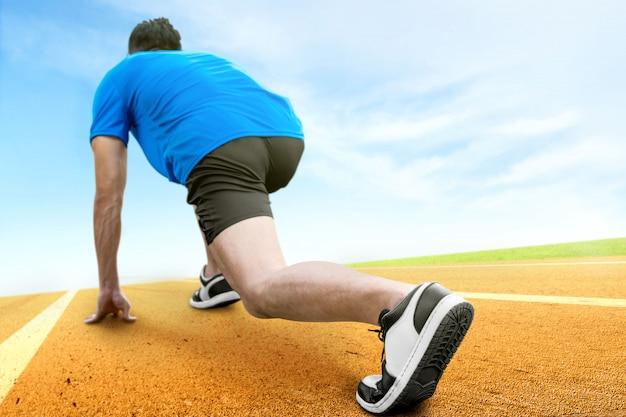 Retrovisione dell'uomo asiatico del corridore pronto a correre sulla pista corrente