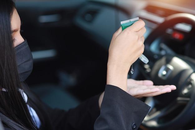 Vista posteriore mani di donna asiatica in abito nero da lavoro con maschera protettiva per uso sanitario disinfettante per le mani con gel alcolico per l'igiene in automobile e guida di auto. nuovo concetto di distanza normale e sociale
