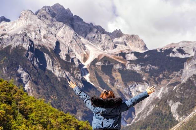 Vista posteriore della viaggiatrice asiatica alza due mani sulla montagna di neve del drago di giada