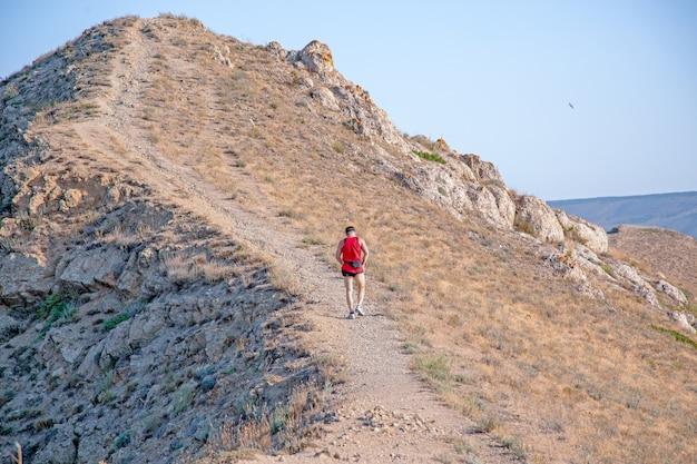 Retrovisione del corridore atletico che corre su una traccia di montagna su un cielo blu