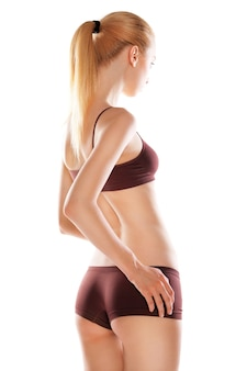 Vista posteriore di una bella donna caucasica bionda con i capelli lunghi in abbigliamento sportivo, isolata su sfondo bianco