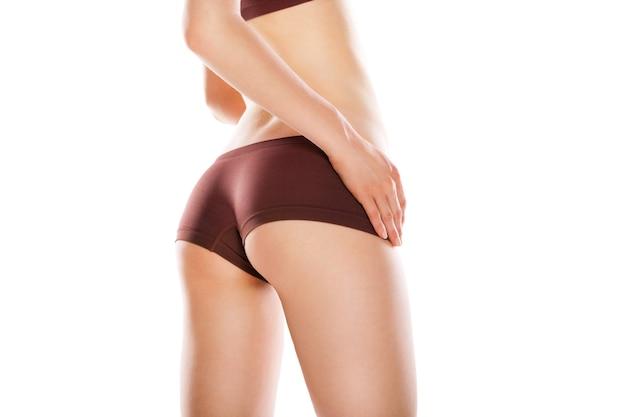 Vista posteriore di una bella donna caucasica con le gambe lunghe, isolata su sfondo bianco