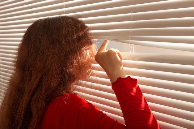 Vista posteriore di bella giovane donna con capelli lunghi fa capolino attraverso il foro nelle persiane della finestra e guarda fuori dalla finestra. concetto di sorveglianza e curiosità