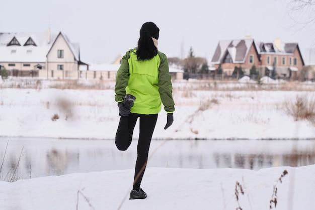 Vista posteriore della donna castana facendo esercizio di allungamento quad mentre allunga la gamba al litorale del fiume invernale