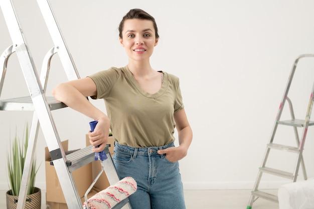Vista posteriore della donna bruna in jeans seduta con rullo di vernice sul gradino della scala e guardando il muro dipinto