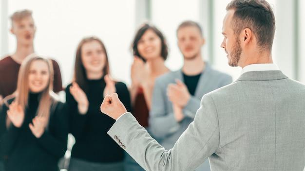Retrovisore. uomo d'affari in piedi di fronte ad applaudire la squadra di affari