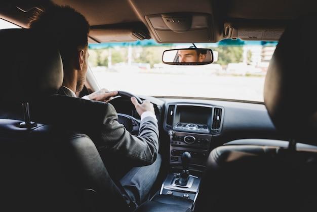 Vista posteriore dell'uomo d'affari che guida l'auto