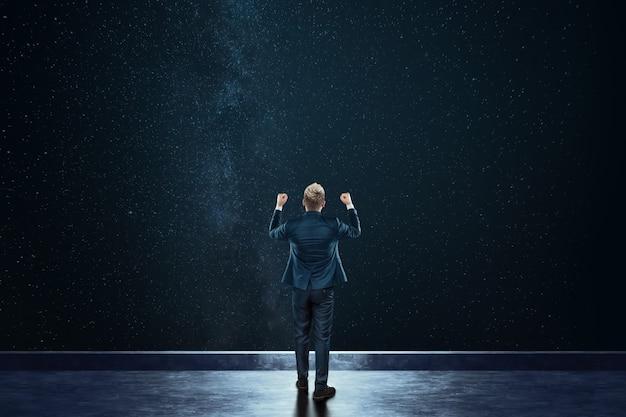 L'uomo d'affari di retrovisione sta contro lo sfondo del cielo stellato