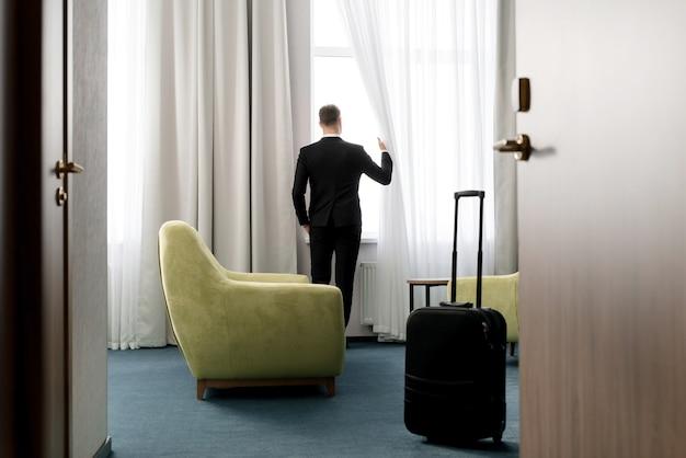 Vista posteriore dell'uomo d'affari che indossa l'abito scuro in piedi nella camera d'albergo che esamina la finestra