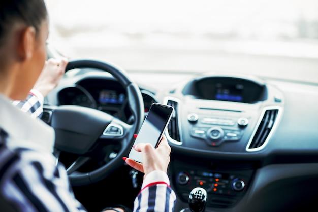 Vista posteriore della donna di affari che tiene mobile mentre si guida un'auto.