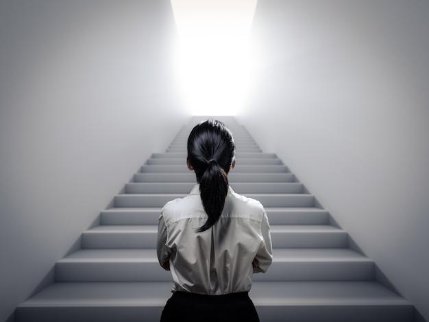 Donna d'affari vista posteriore in piedi alle scale