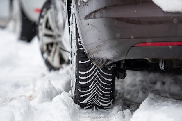 Vista posteriore dell'auto con pneumatici invernali in strada innevata, primo piano