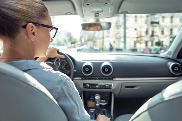 Vista posteriore di una donna d'affari caucasica seduta al volante della sua auto che guida in sicurezza