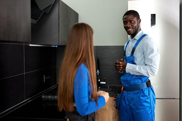Vista posteriore la donna del cliente è grata all'idraulico afro sorridente per il problema tecnico di riparazione in cucina, bel tuttofare fiducioso in tuta blu che parla con il cliente femminile, discutendo la riparazione. a casa