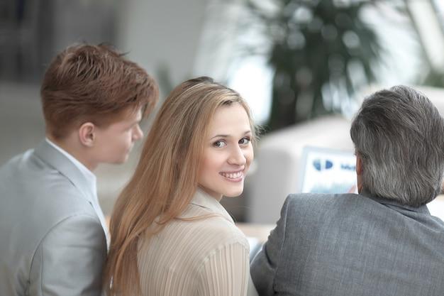 Vista posteriore.close up. giovane donna d'affari guardando la fotocamera.