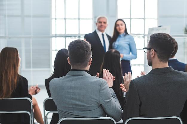 Retrovisore. dipendenti dell'azienda che applaudono durante una riunione di lavoro. concetto di successo