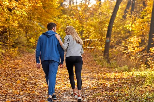 Vista posteriore sulle coppie che godono di fare jogging su una strada di campagna attraverso la bellissima foresta di autunno