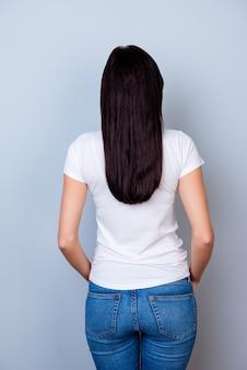Vista posteriore della giovane donna carina su uno spazio grigio