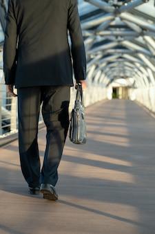 Vista posteriore del delegato o dell'uomo d'affari che porta una borsa in pelle nera mentre si sposta lungo il corridoio davanti alla telecamera all'interno del centro affari