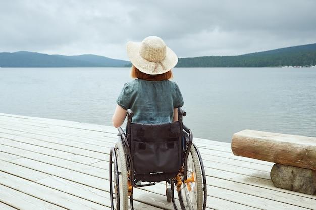 Vista posteriore di una donna disabile che si gode la splendida vista del paesaggio marino