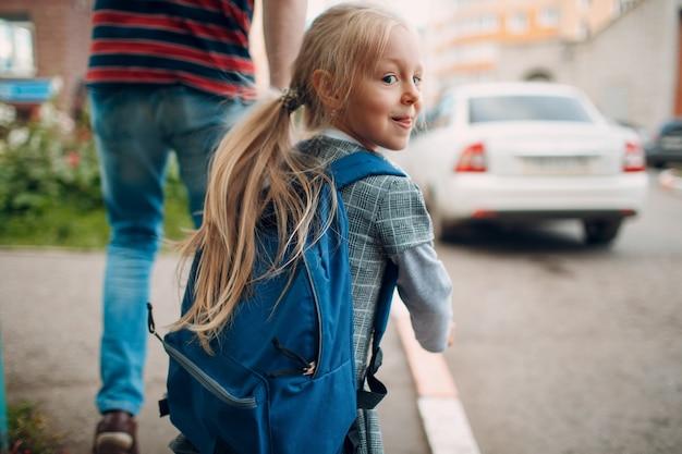 Vista posteriore del padre che torna a scuola con sua figlia che trasporta lo zaino.