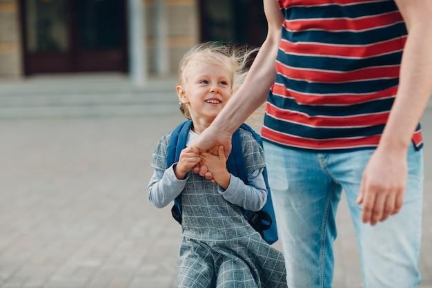 Vista posteriore del padre che torna a scuola con sua figlia che porta lo zaino