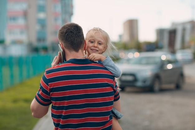 Vista posteriore del padre che torna a scuola con la sua piccola figlia.