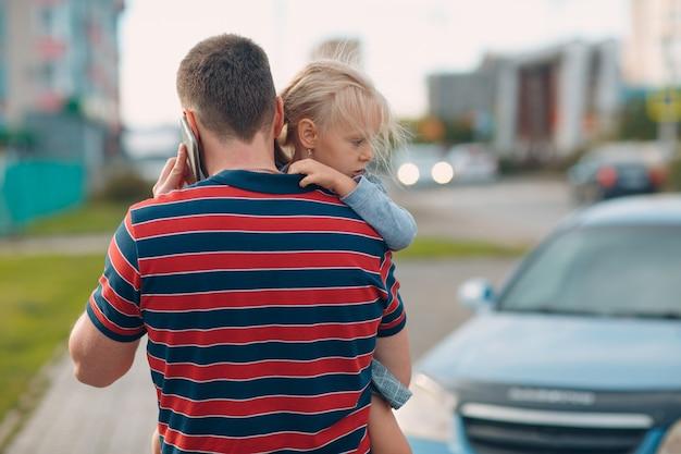 Vista posteriore del padre che cammina al centro per l'infanzia con la sua piccola figlia.