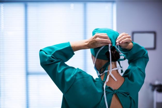 Retrovisione del chirurgo femminile che indossa il teatro in funzione della maschera chirurgica