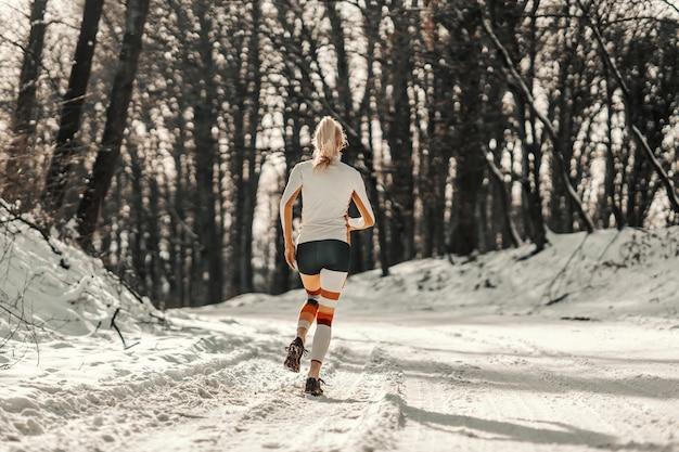 Vista posteriore di una sportiva in forma in esecuzione su sentiero innevato in natura in inverno. sport, esercizi cardio, fitness invernale