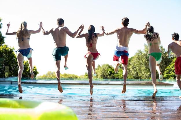 Vista posteriore di amici che saltano in piscina