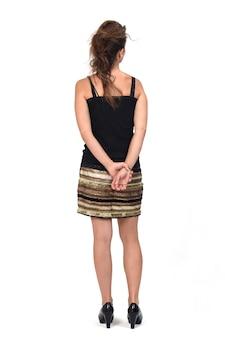 Vista posteriore di un ritratto completo di una donna in una gonna, mani incrociate