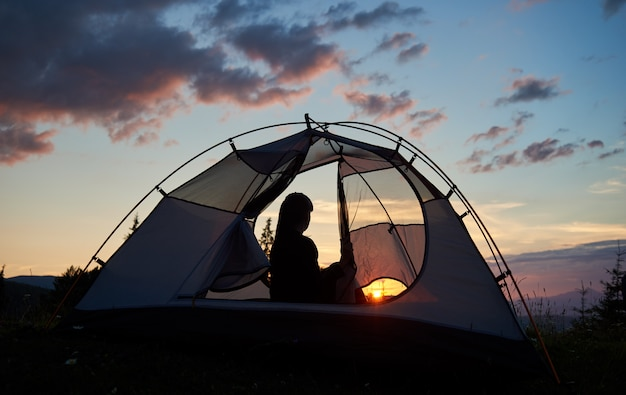 Viandante della ragazza di retrovisione che si siede in una tenda sotto il cielo blu di mattina che gode dell'alba sul sol levante luminoso