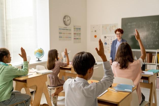 Vista posteriore di un gruppo di compagni di classe interculturali che alzano la mano a lezione