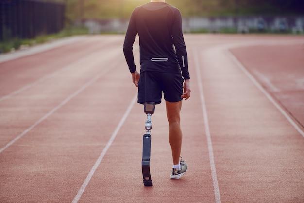 Vista posteriore del giovane handicappato caucasico bello con la gamba artificiale e vestito in pantaloncini e felpa che cammina sulla pista.