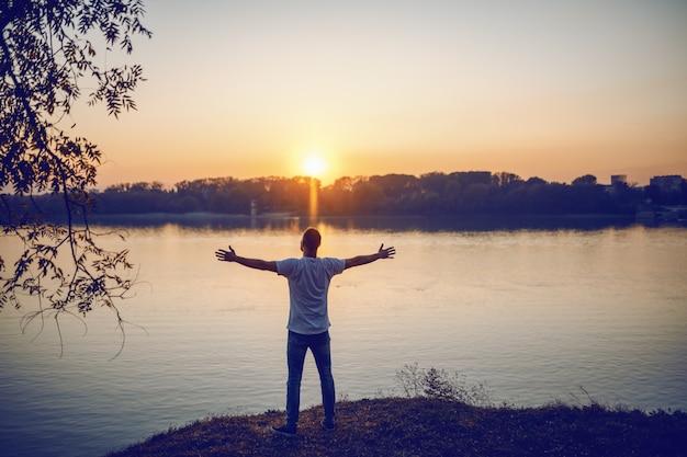 Vista posteriore dell'uomo caucasico bello in piedi con le braccia aperte sulla scogliera e guardando il fiume e il bellissimo tramonto.