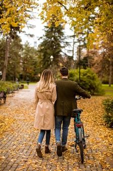 Vista posteriore di una bella coppia giovane nel parco autunnale con bicicletta elettrica