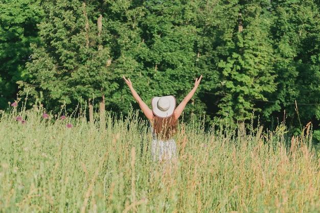 La vista posteriore di una giovane donna felice con i capelli lunghi in cappello e vestito alza le braccia mentre cammina