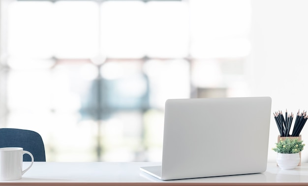 Vista posteriore del computer portatile sul tavolo bianco con sfondo sfocato della stanza bianca.